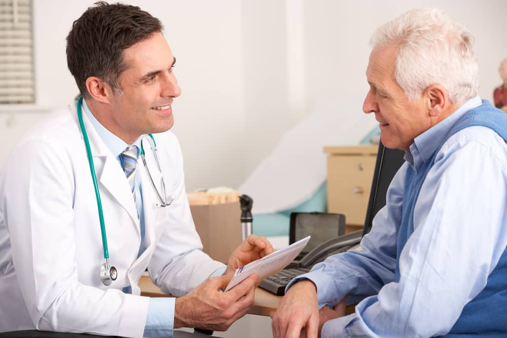 American,Doctor,Talking,To,Senior,Man,In,Surgery