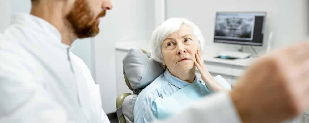 Worried,Elder,Woman,During,The,Consultation,With,Handsome,Dentist,Showing