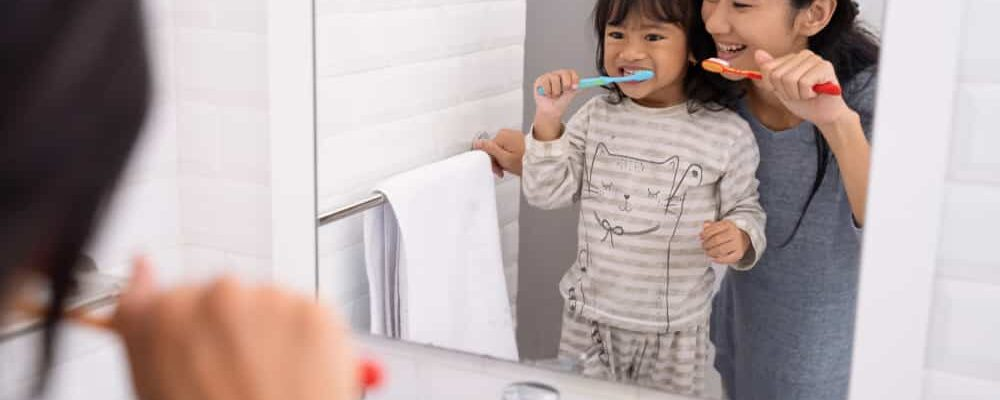 Beautiful,Mother,And,Daughter,Brushing,Teeth,In,The,Bathroom,Sink