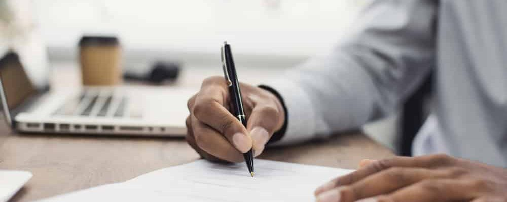 Young,Man,Signing,An,Official,Document,,Male,Hand,Holding,Pen