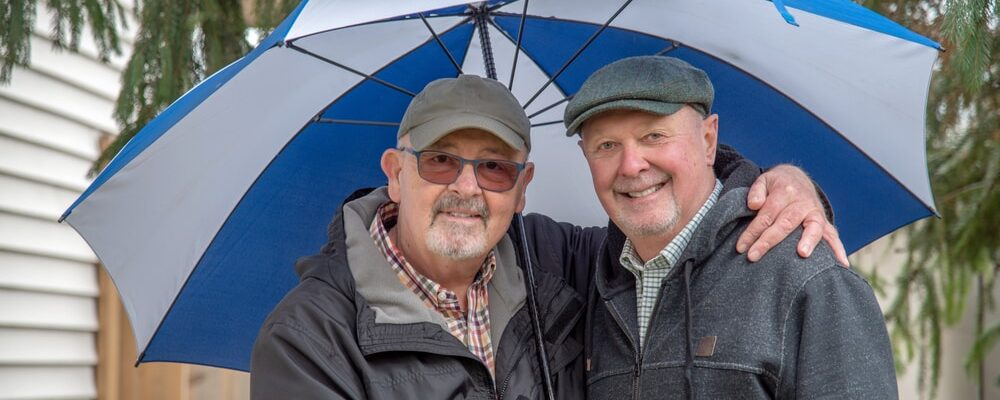 Older,White,Male,Gay,Couple,Under,An,Umbrella.