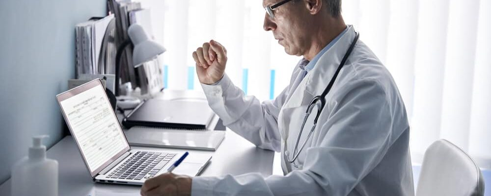 Serious,Mature,Old,Doctor,Physician,Using,Laptop,Tech,In,Hospital