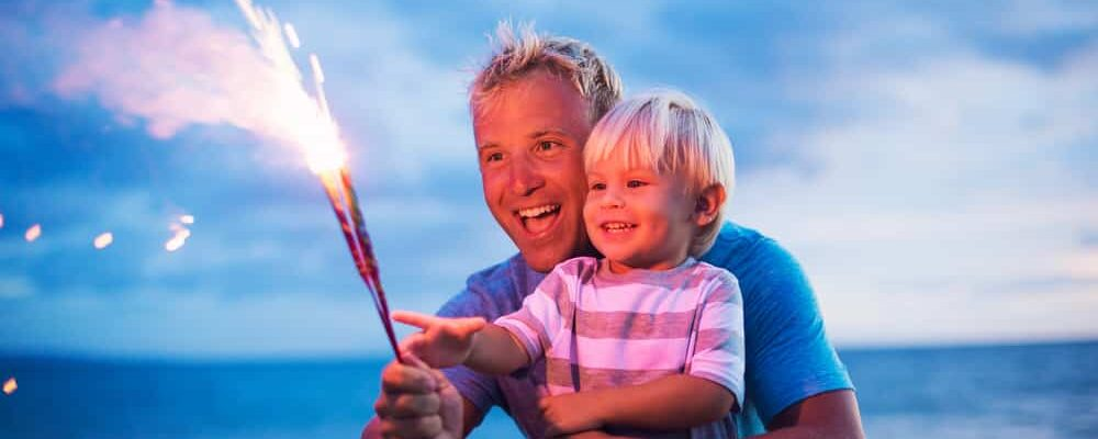 Father,And,Son,Lighting,Sparklers,On,The,Beach,At,Sunset