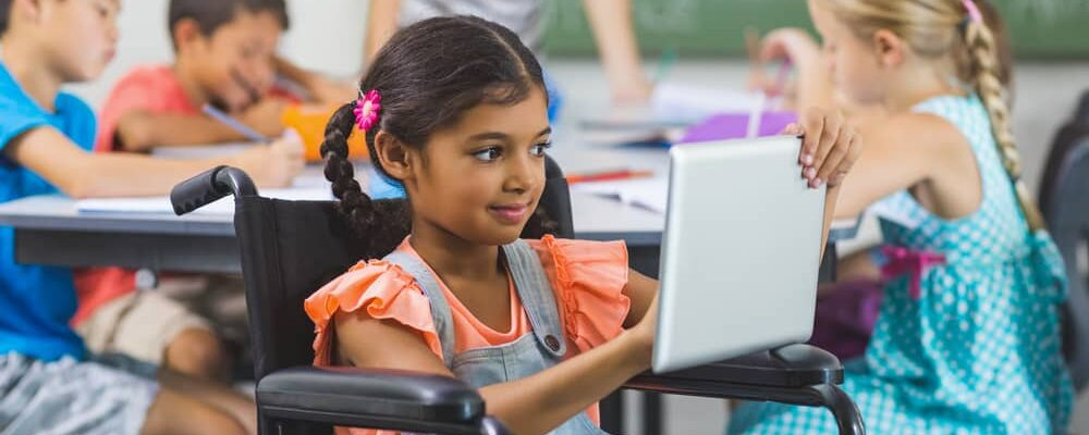 Disabled,Schoolgirl,Using,Digital,Tablet,In,Classroom,At,School