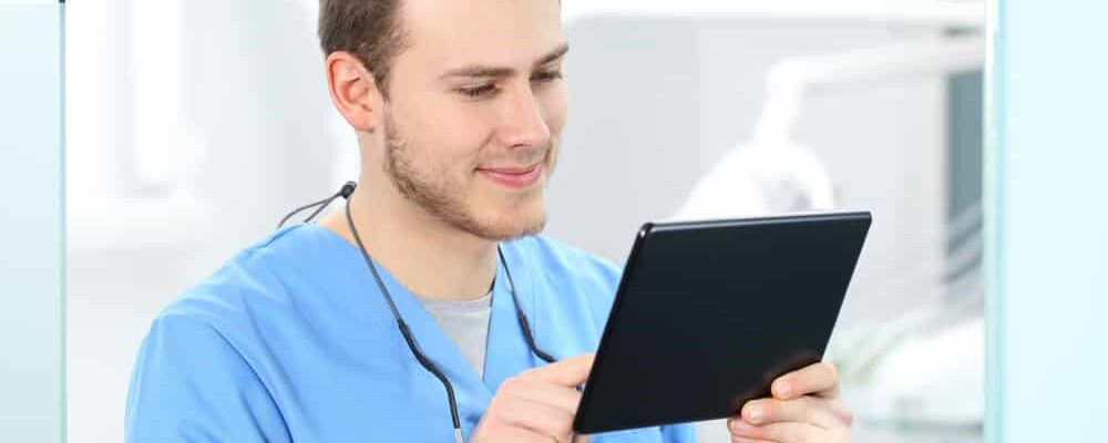 Doctor,Wearing,Blue,Coat,Working,On,Line,With,A,Tablet