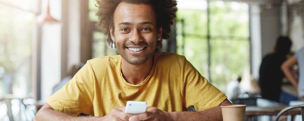 Happy,Dark-skinned,Male,Student,Wearing,Yellow,T-shirt,Sitting,At,Coffe