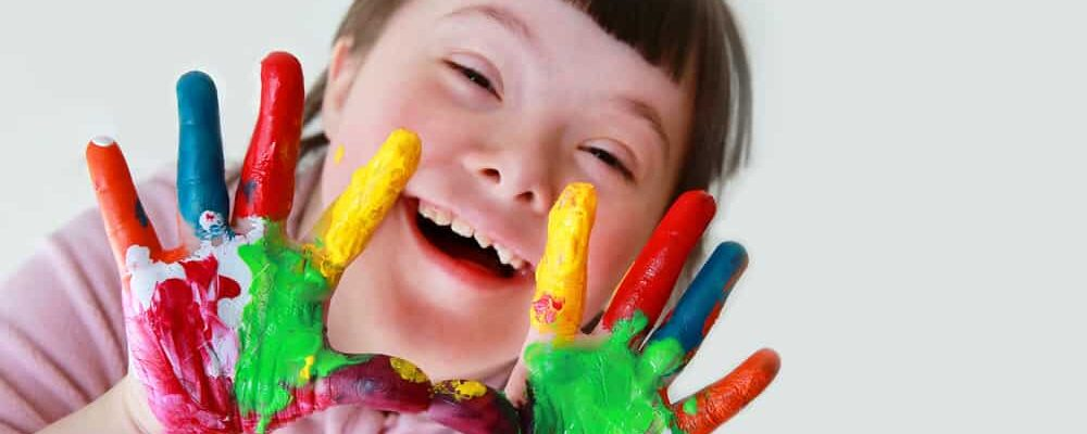 Cute,Little,Down,Syndrome,Girl,With,Painted,Hands.