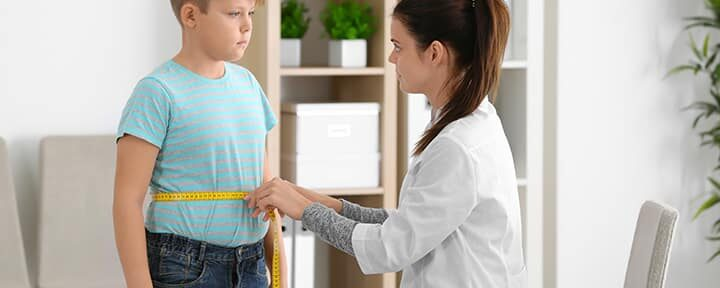 Female doctor measuring waist of overweight boy in clinic